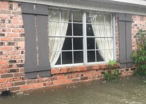 Exterior view of flooded house before renovation.